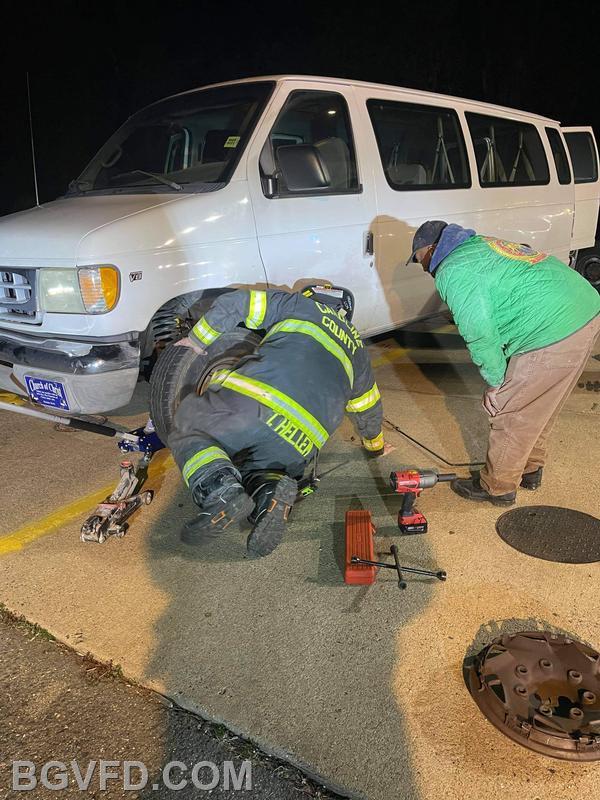 Firefighter T. Hellem assists a citizen change a flat tire after the incident.